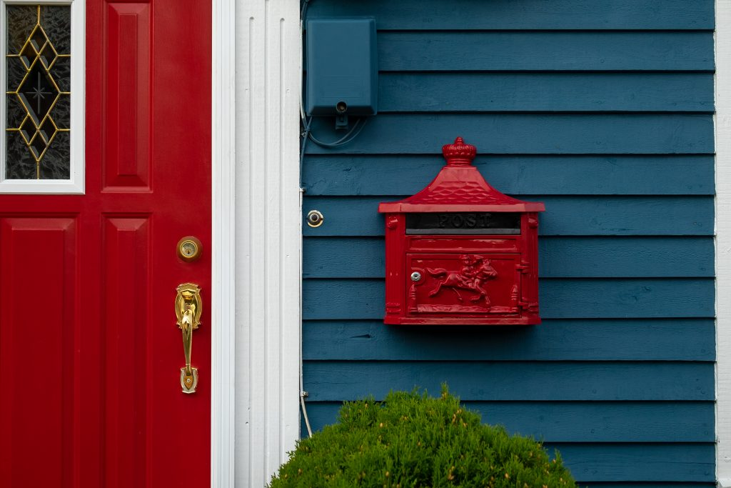 A colorful red and blue house with the front door and mailbox in the picture
