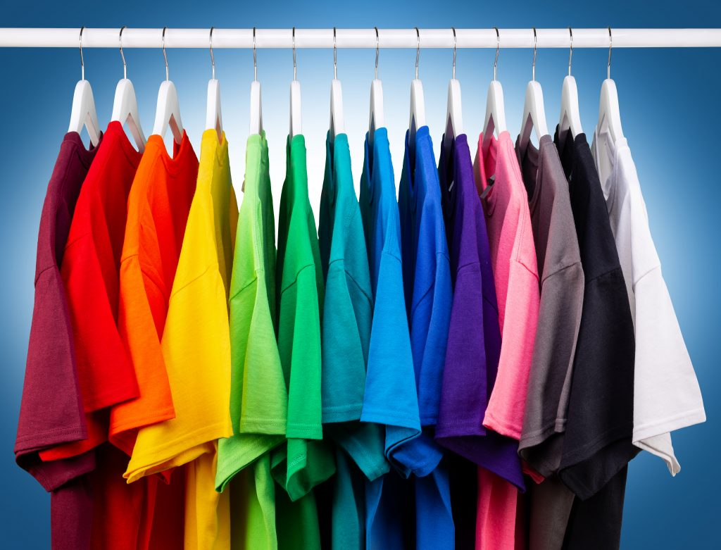 14 tee shirts in the colors of the rainbow hanging on a closet rod